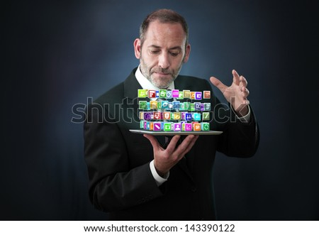 a mature businessman wizard conjures a lots of apps flying around his pad or tablet PC - stock photo