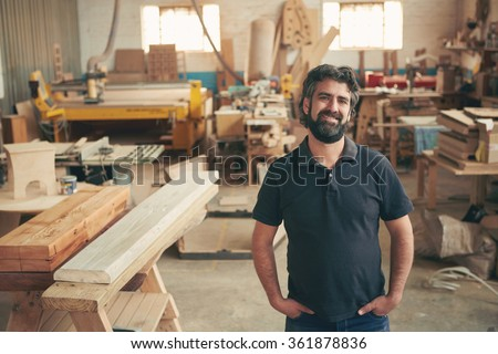 A mature carpenter standing confidently in his workshop - stock photo