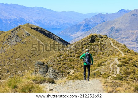 A mature caucasian hiker with backpack on the slope of Ben Lomond, Queenstown New Zealand - stock photo