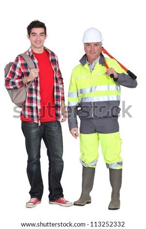 A mature construction worker and his grandson. - stock photo