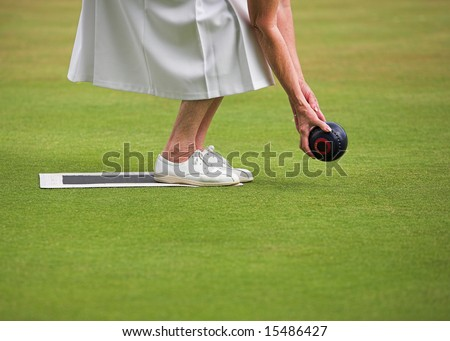 A mature lady player playing lawn bowls. - stock photo