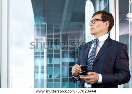 A mature man with a coffee in the office - stock photo