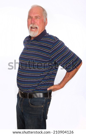 A mature man yelling in pain as he holds his lower back - stock photo