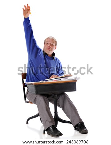 A mature student vigorously raising his hand while sitting in a retro child's school desk.  On a white background. - stock photo