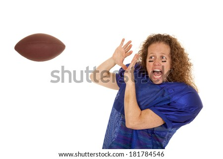 A mature woman afraid to catch a football.