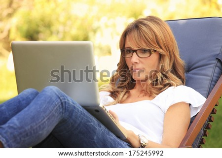A mature woman sitting in garden at home and working on her laptop. - stock photo