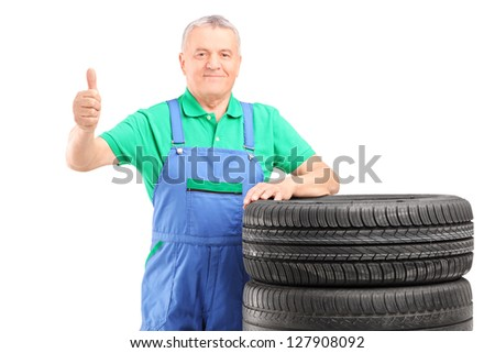 A mature worker posing on car tires and giving thumb up isolated on white background - stock photo
