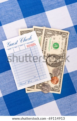 A meal check from a restaurant with change on a checkered table cloth