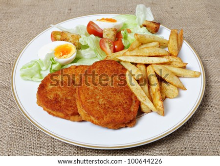 A meal of chicken burgers with french fried potato chips and a tomato, egg and lettuce salad