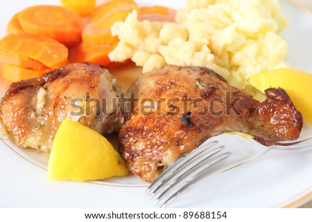 A meal of chicken thighs, marinaded in lemon juice and herbs and then roasted, served with mashed boiled potatoes and boiled carrots - stock photo
