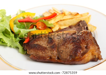A meal of pan-seared T-bone steak with french fries and a salad of lettuce, rocket, capsicum slices and cherry tomatoes - stock photo