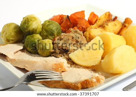 A meal of roast turkey with all the trimmings - brussels sprouts, roast sweet potatoes, roast parsnips stuffing and boiled potatoes