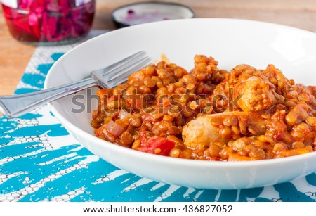 A meal of sausages and lentil casserole in a white bowl with a fork - stock photo