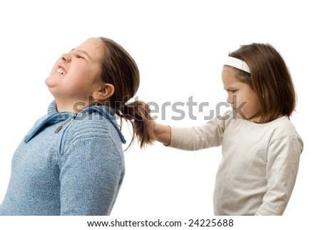 A mean little girl pulling on her older sister's hair, isolated against a white background - stock photo