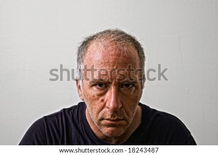 a mean looking man staring directly at viewer - stock photo