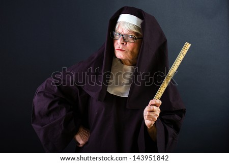 A mean looking nun with a ruler - stock photo