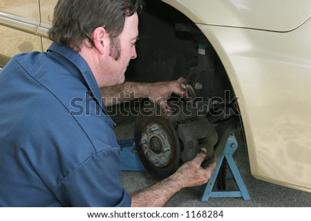 A mechanic adjusting front disc brakes. - stock photo