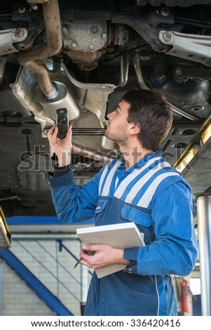 A mechanic, checing a muffler on an exhaust system of a modern car on a car lift using a LED flashlight, for gas leaks during a periodic inspection or MOT test - stock photo