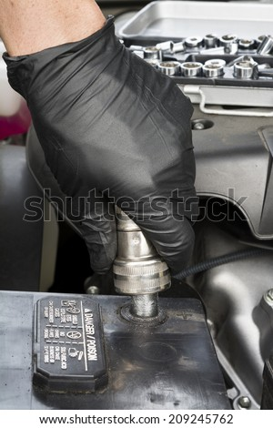 A mechanic cleans a battery terminal with a wire battery terminal brush during routine automobile maintenance.  - stock photo