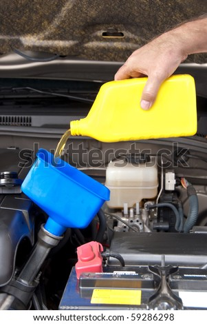 A mechanic pours fresh oil into a car engine as part of its maintenance. - stock photo