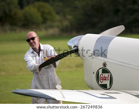 a mechanic swings the propeller to start a vintage aircraft at the Shuttleworth Collection,Bedfordshire,UK. taken 26/09/2014 - stock photo