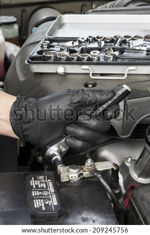 A mechanic tightens a battery terminal cable to a lead battery post after cleaning it with a wire brush during routine automobile maintenance.  - stock photo