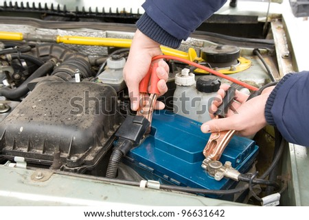 A mechanic using jumper cables to start a car battery. - stock photo