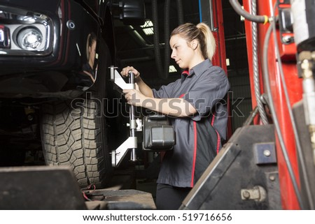 A Mechanic woman working on car in his shop