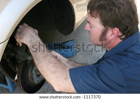 A mechanic working on a car's brakes. - stock photo