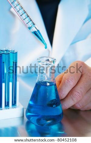 a medical research scientist or chemist works in a laboratory. light in a blue light. blue being a popular color for health, science, calm, relaxation, and just generally a great cool color - stock photo