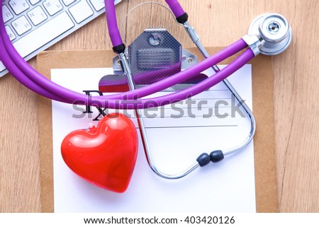 A medical stethoscope near a laptop on a wooden table - stock photo