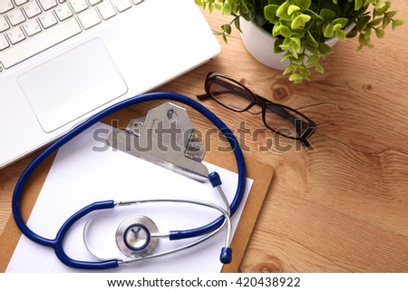A medical stethoscope near a laptop on a wooden table, on white - stock photo