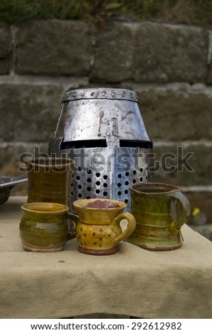 A Medieval Knights helmet on a hessian covered table with pottery cups and jars. - stock photo