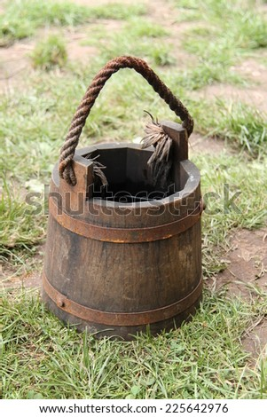 A Medieval Style Wooden Bucket with a Rope Handle. - stock photo