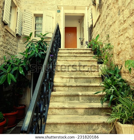 A mediterranean stone medieval house with doorway, steps, railings, window shutters and pot plants (Italy). Square toned image, instagram effect - stock photo