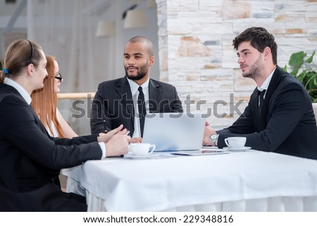 A meeting of the Board. Four smiling successful businesspeople at meeting, sitting at table in office while discussing business matters.