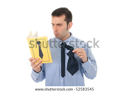 A men in his thirties fails at tying his necktie while reading a book about how to do it. - stock photo