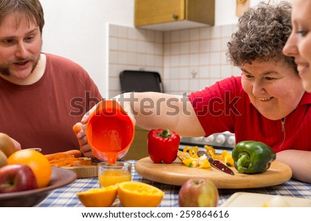 a mentally disabled woman and two caretakers cooking together - stock photo