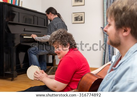 a mentally disabled woman learning a music instrument - stock photo