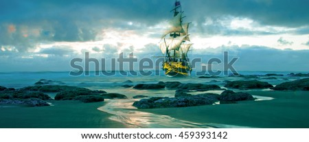 A merchant marine sail ship sailing dangerously close to rocks and the beach. - stock photo