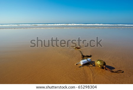 a message bottle run ashore and stuck on an anchor rope with a buoy - stock photo