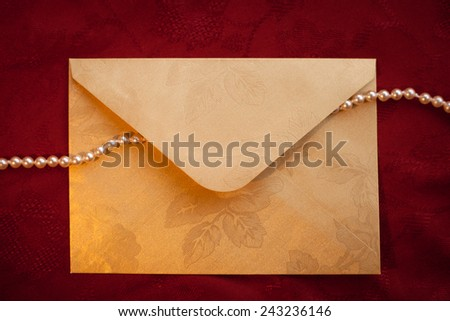 A message of luxury: golden envelope with pearls against floral red texture