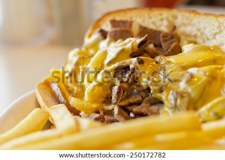A messy Philly Cheesesteak with onions and peppers with fries on the side