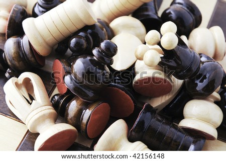 a messy pile of pieces on a chessboard - stock photo