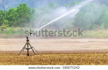 A metal automatic water sprinkler in the vast field, Nozzles are watering the field - stock photo