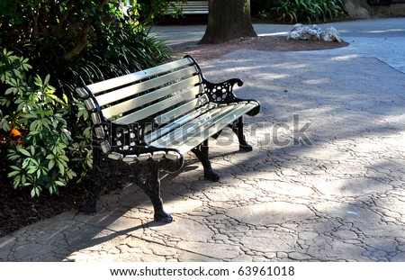 A metal bench painted beige, in a park - stock photo