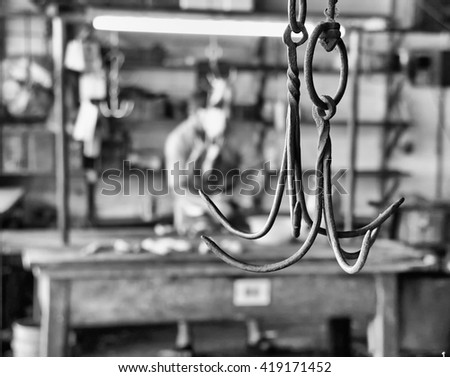 A metal butcher's hook in an abattoir. Processed in monochrome.