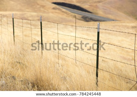 barbed wire fence cattle. A Metal Cattle Fence And Barbed Wire Fencing On Rolling Brown Grass Hill, At