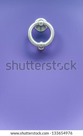 A metal door knocker on a purple door - stock photo