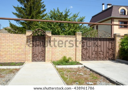 A metal gate in a brick wall - stock photo